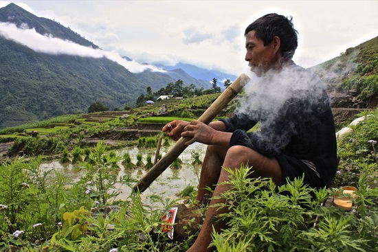 a Black Hmong man takes a break from working in the rice terraces outside of Sapa