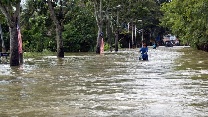 File photo of people wading through floodwaters in the northern Malaysian state of Perlis, in November 2010