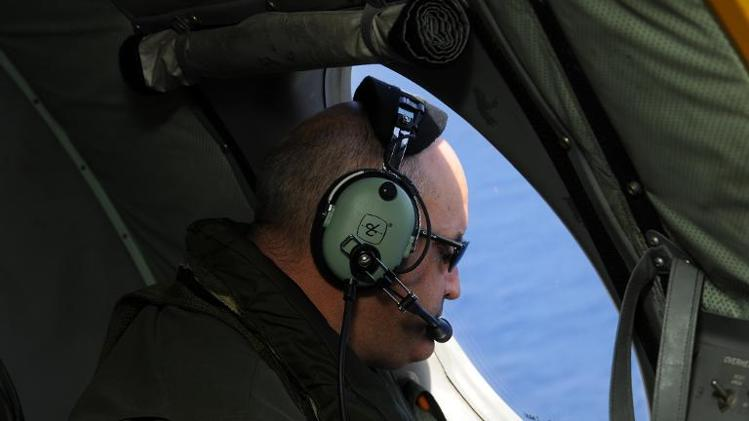A crew member on a Royal New Zealand Airforce P-3K2-Orion aircraft searches for Flight MH370 off Perth on April 13, 2014