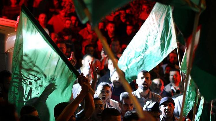 People wave Hamas flags after the remains of four Palestinians were returned from Israel, in the early hours of April 30, 2014 in Al-Bireh