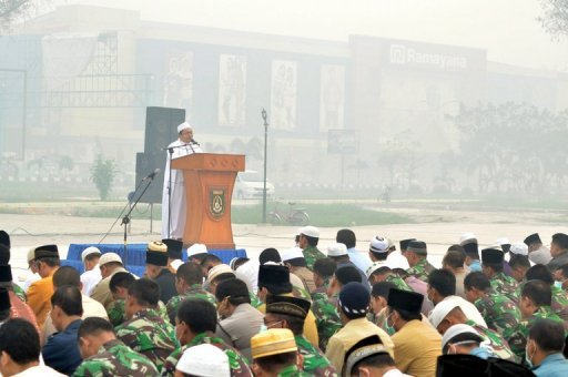A Muslim cleric leads Indonesian officials and residents in mass prayers asking for rain, at a square covered in thick haze in Dumai, on June 25, 2013.
