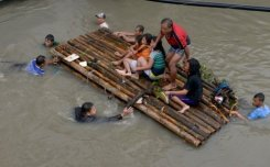 Residents ride on a bamboo raft over floodwaters in the farming town of Novaleta, on August 19, 2013. Torrential rain has hit large parts of the Philippine capital and surrounding areas for a second day.
