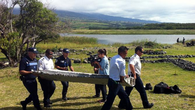 Police carry a piece of debris from an unidentified aircraft found on the French Indian Ocean island of La Reunion on July 29, 2015