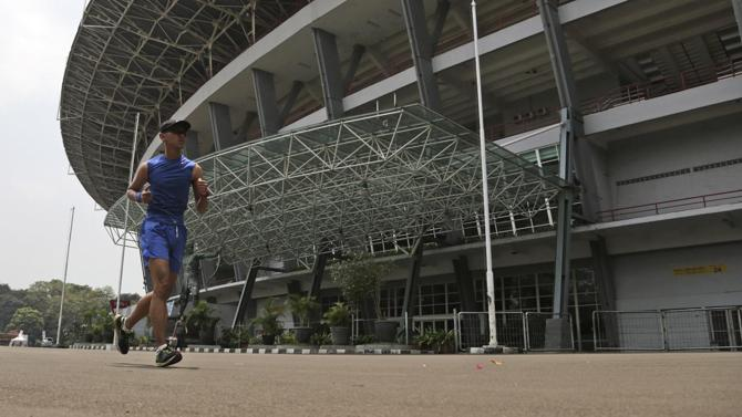 In this Thursday, Sept. 11, 2014 photo, a man runs around Gelora Bung Karno Stadium in Jakarta, Indonesia. Indonesian officials are confident they will return from the Asian Games in Incheon, South Korea, with confirmation that their country will host the next edition of the continental event, pitching a two-city event that could be staged a year ahead of schedule. Vietnam initially was awarded the rights to stage the Asian Games in 2019, but backed out in April citing a lack of funds. Indonesia, Southeast Asia's largest nation and home to a fast-growing economy, has since emerged as the strongest candidate to host the event. (AP Photo/Achmad Ibrahim)