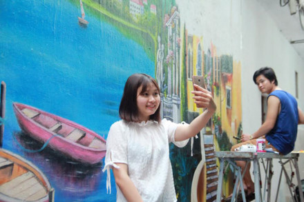 A young girl taking a selfie photo in front of the colourful walls